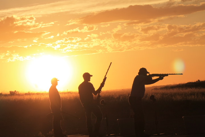 men with guns in front of sunset